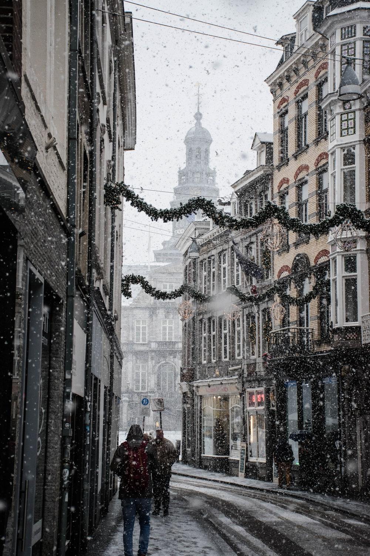 people walking near street between brown building during snow season