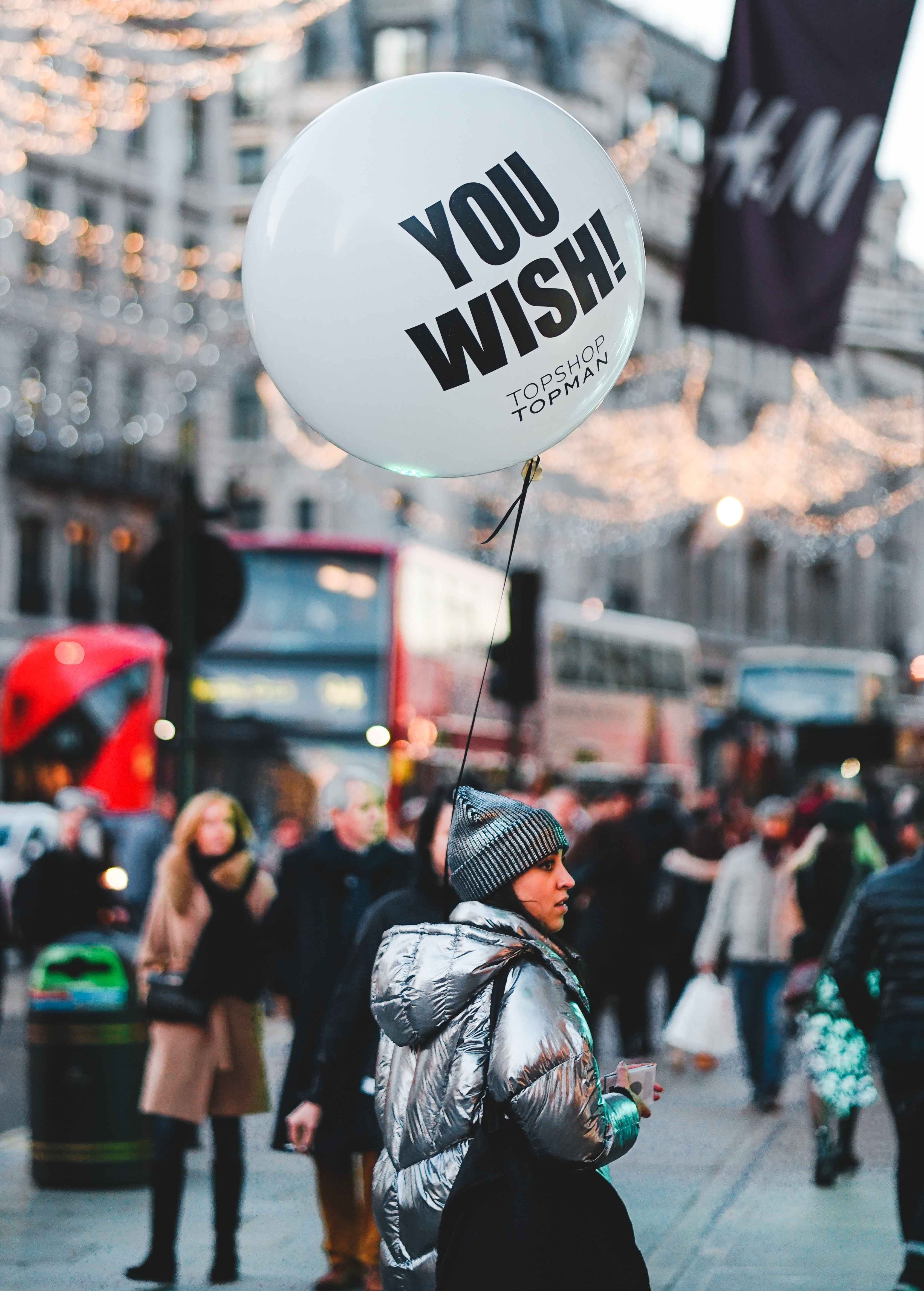 woman walking on street with people holding balloon at daytime