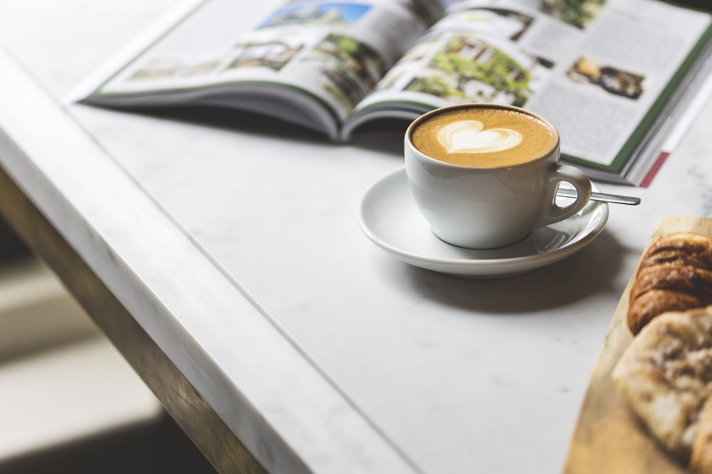 white ceramic coffee cup with saucer on white table