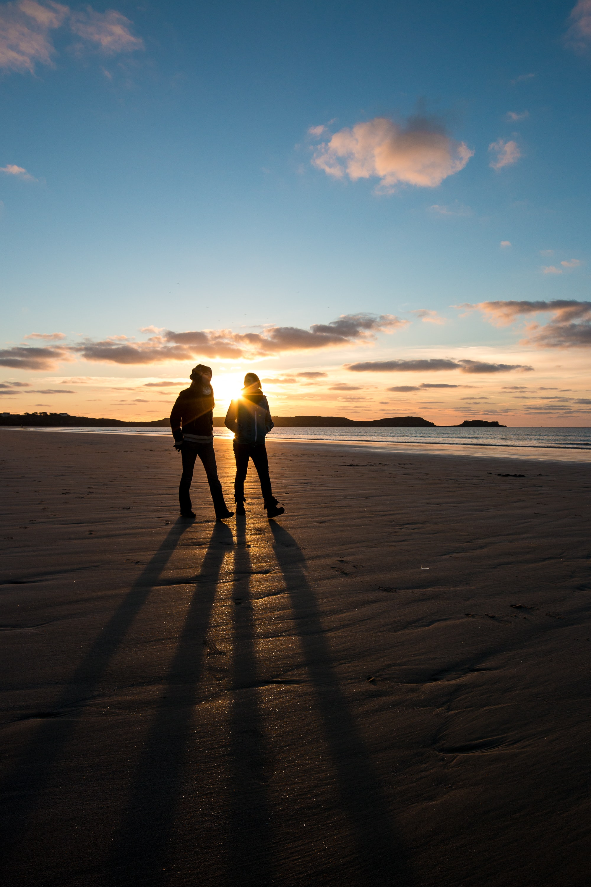 silhouette photo of two persons walking along seashore