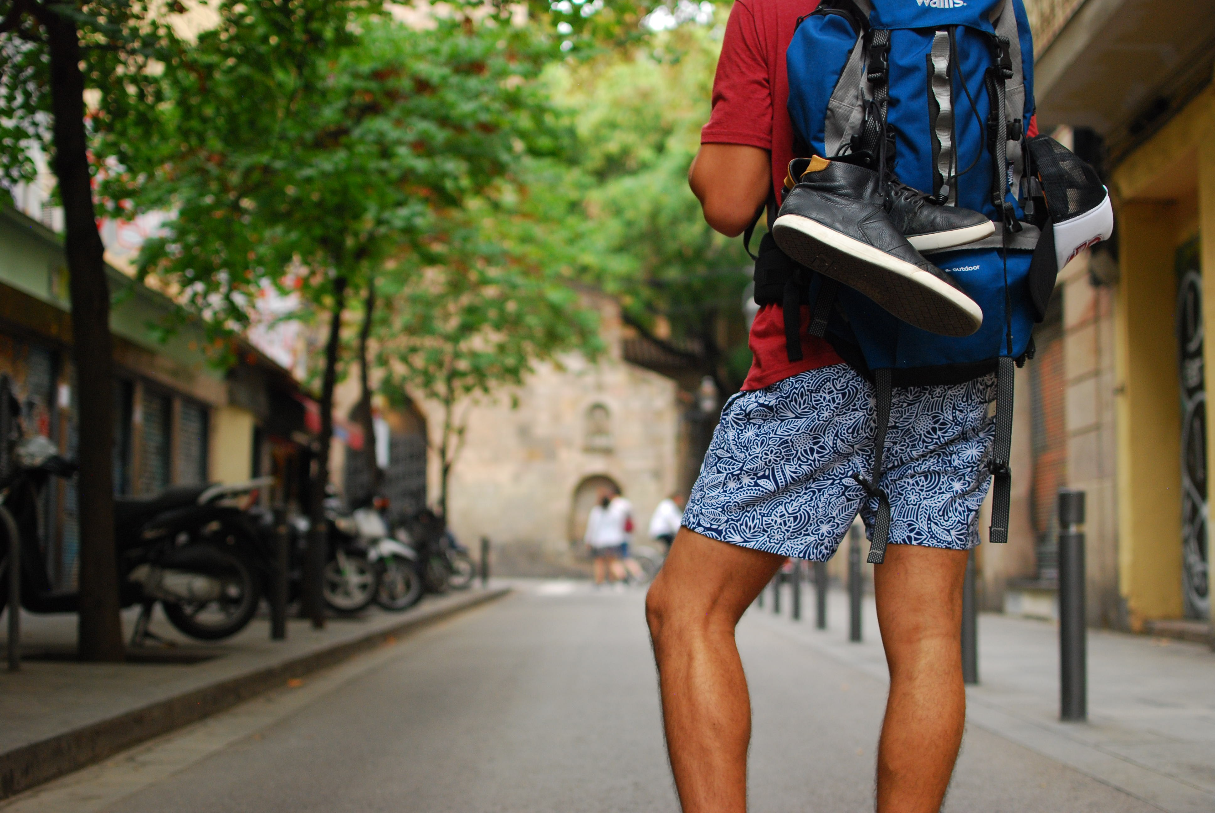 man standing on street carrying backpack
