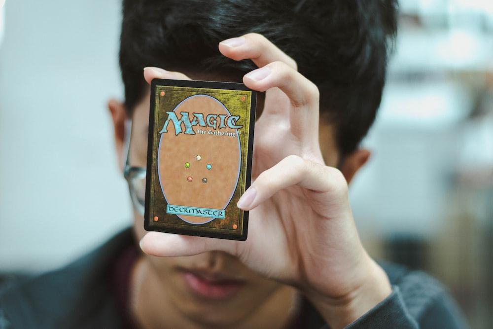 boy holding Magic: The Gathering trading card