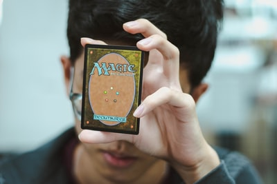 boy holding Magic: The Gathering trading card