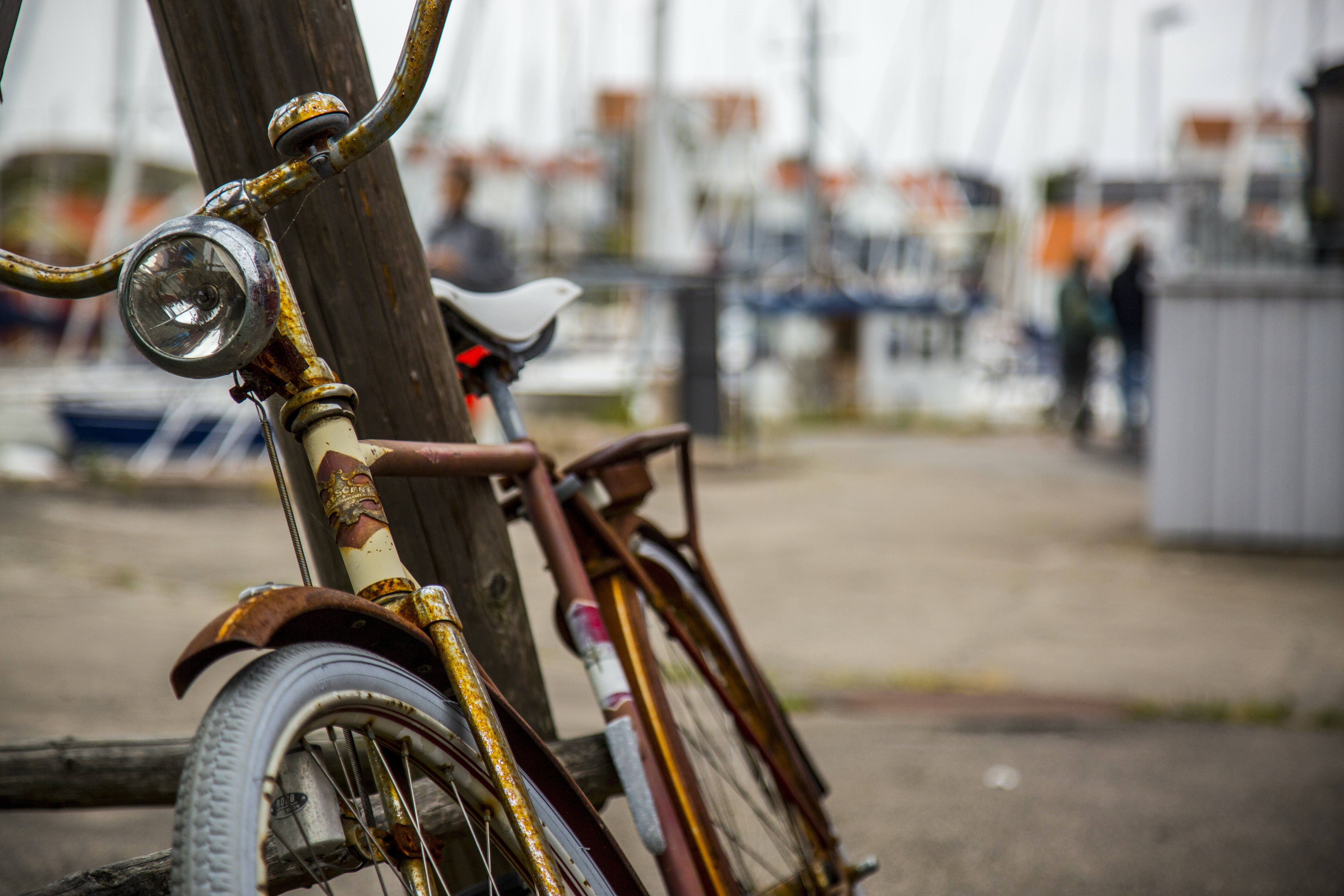 shallow focus photography of city bike leaning on brown wooden post