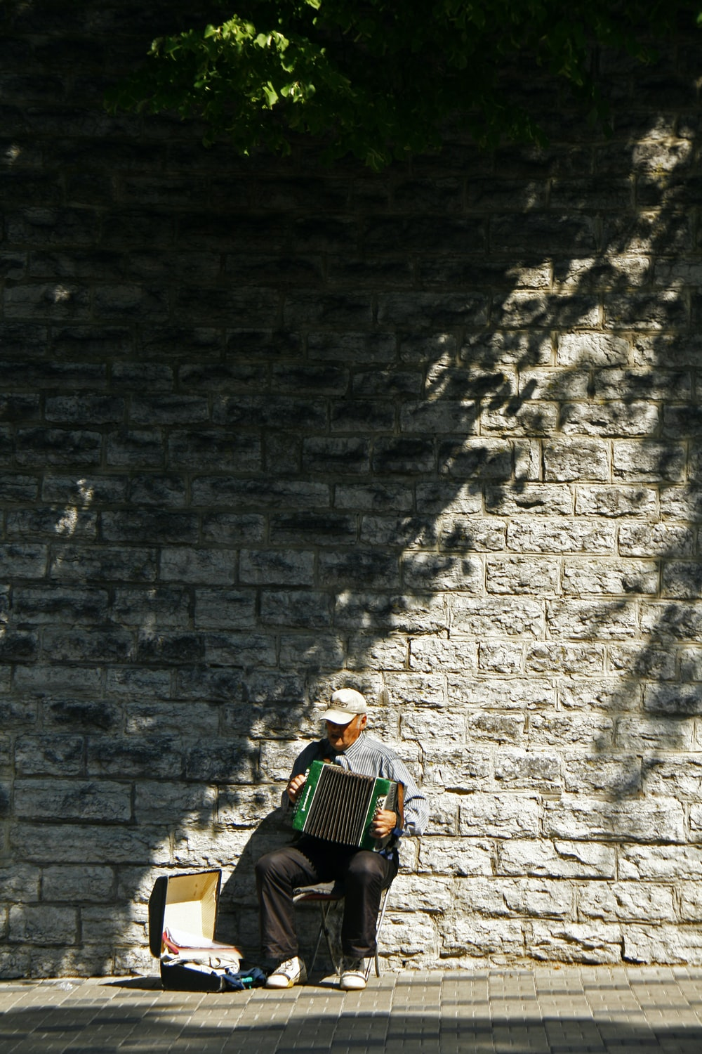 man wearing grey shirt playing accordion instrument while sitting near concrete wall and case during daytime