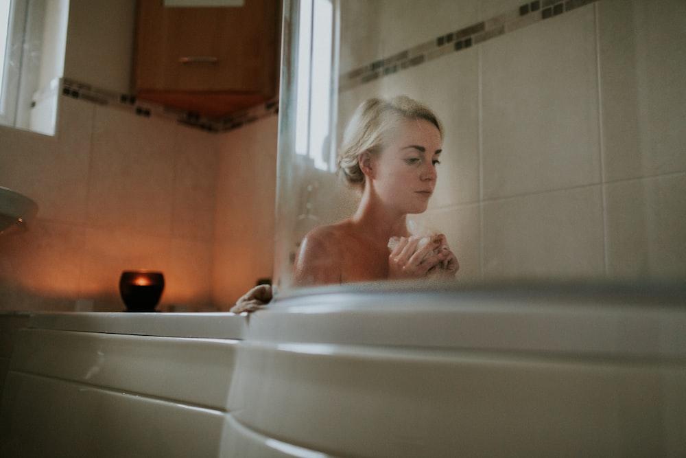 naked woman sitting inside bath tub