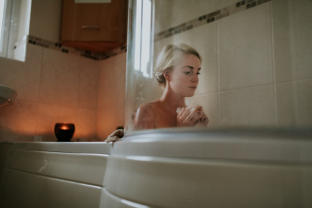 naked woman sitting inside bath tub