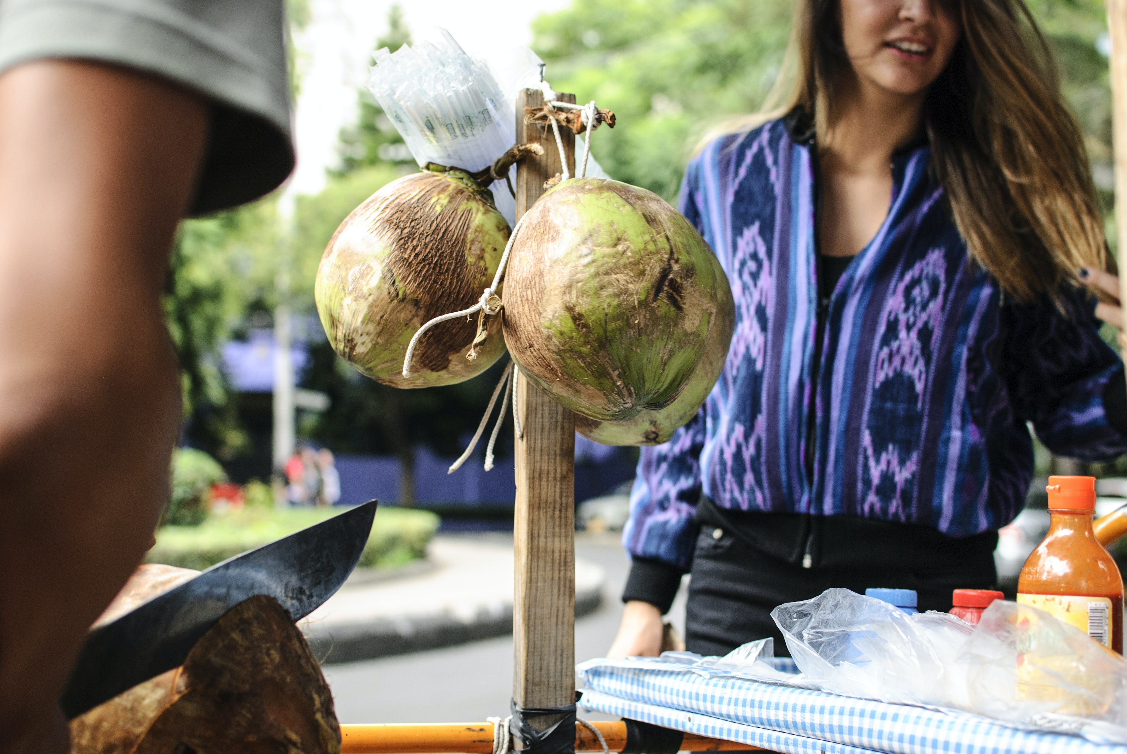 two green coconuts hanging on brown wooden bar