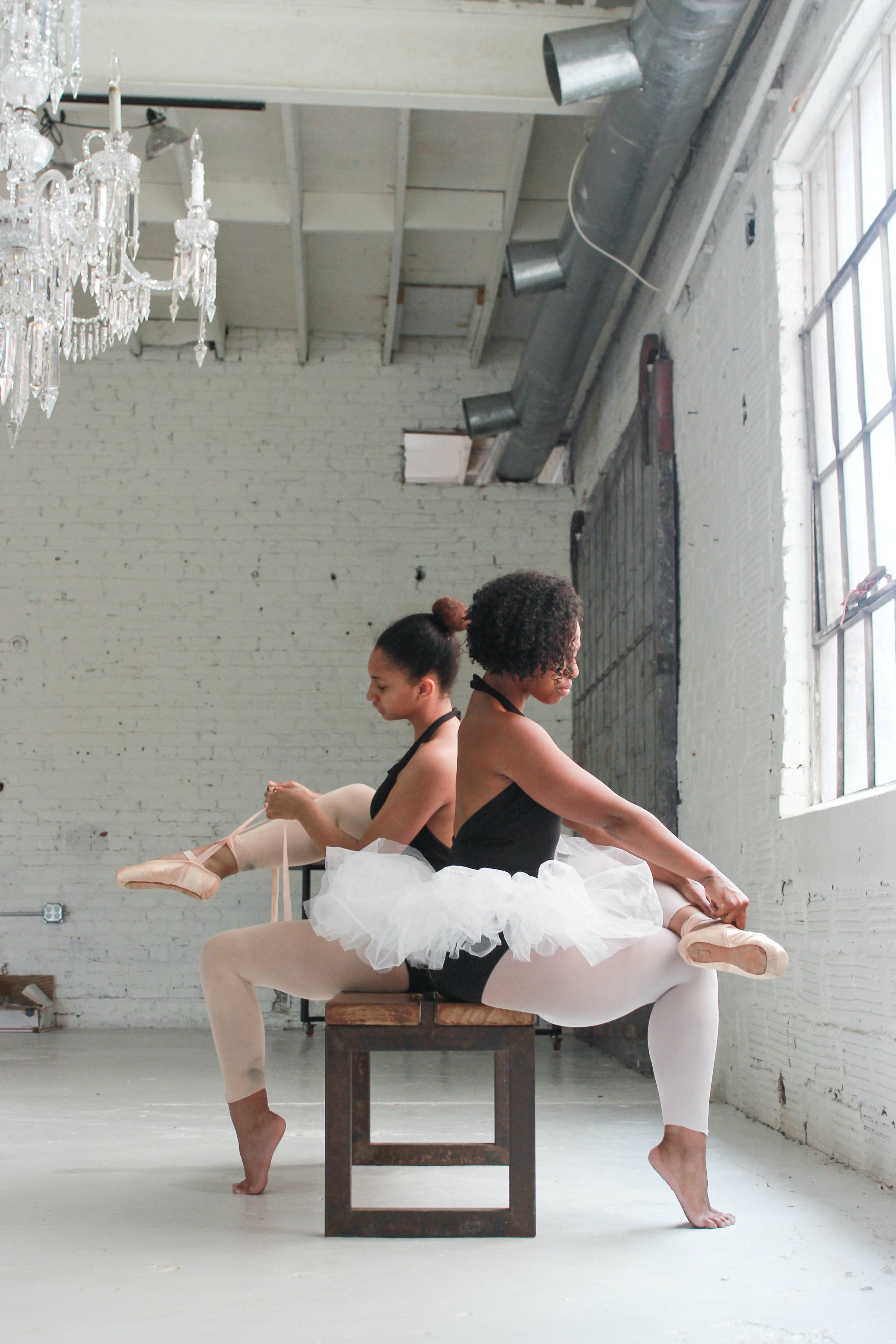 photo of two ballerina tying their shoes