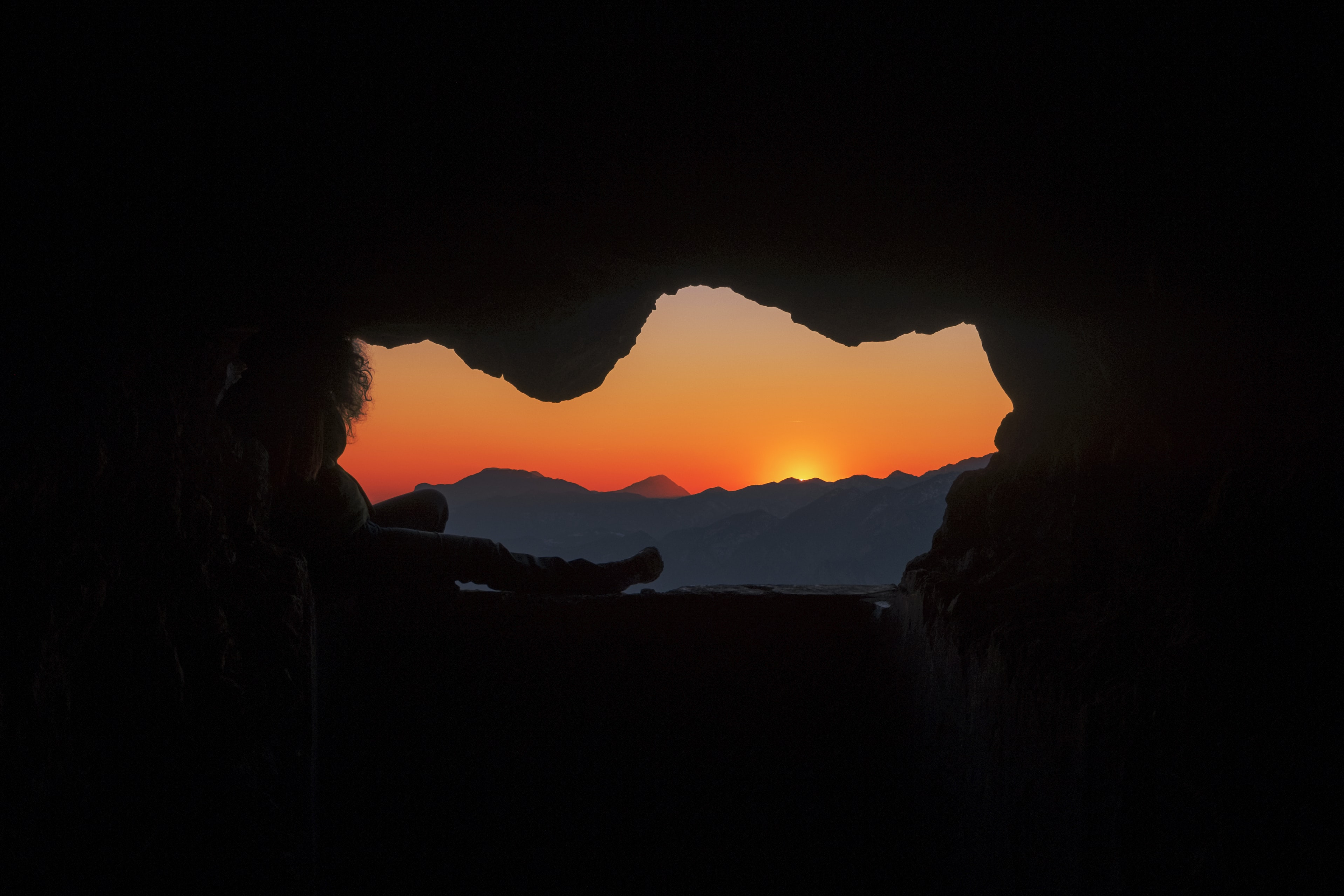 silhouette of person sitting on cave during golden hour