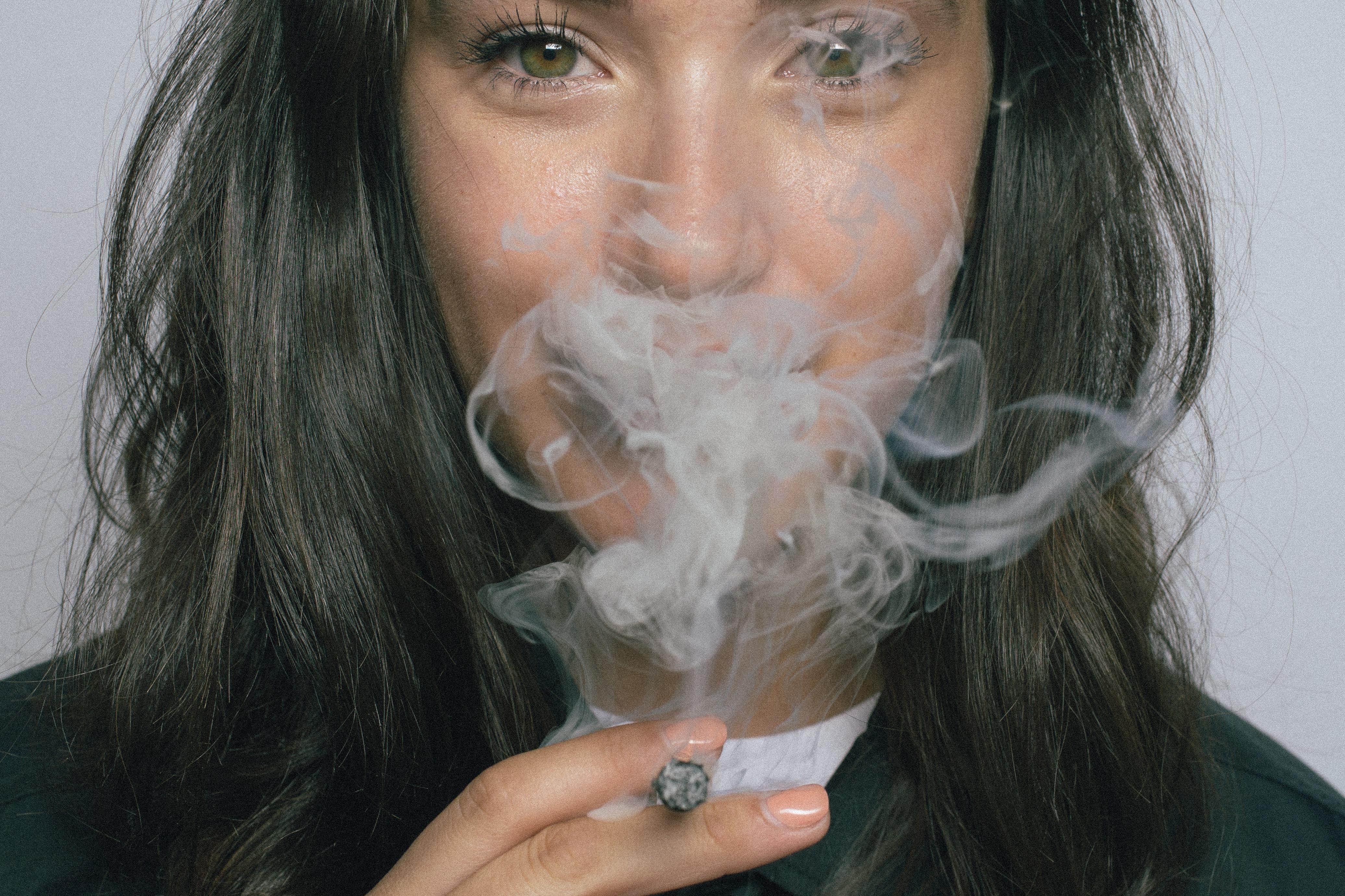 closeup photography of woman smoking cigarette
