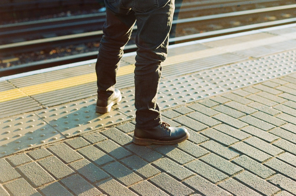 person wearing pair of black work boots standing on concrete blocks