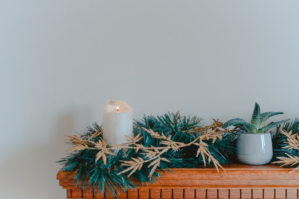 candle with garlands on shelf