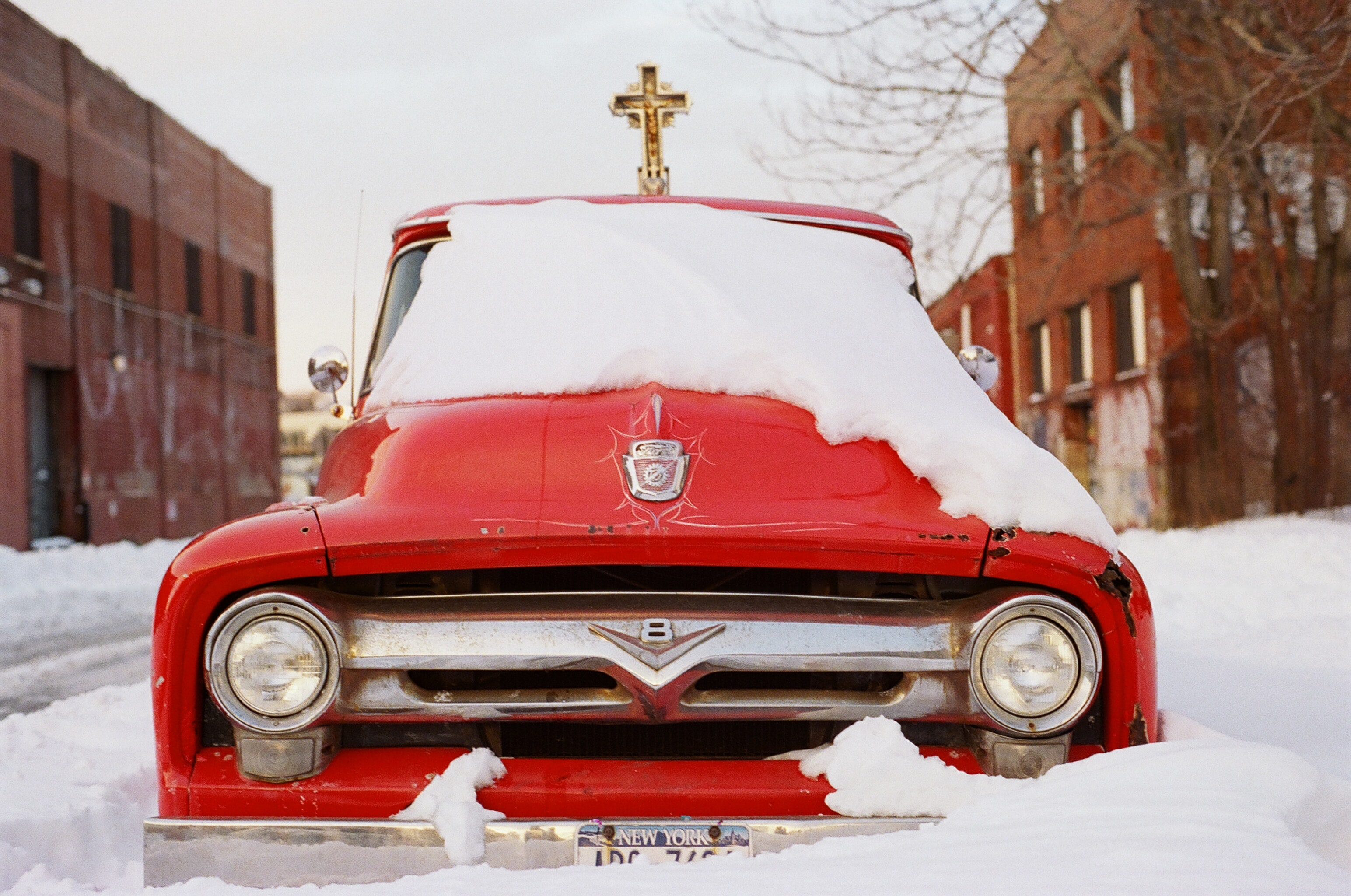 red vehicle surrounded by snowy field beside brown concrete buildings during daytime