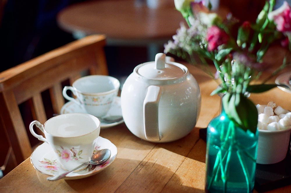 white ceramic teapot and two white teacups on brown wooden table near pink flower centerpiece closeup photography
