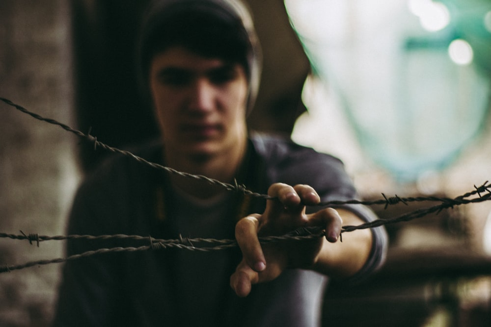 person wearing gray shirt holding barbwire