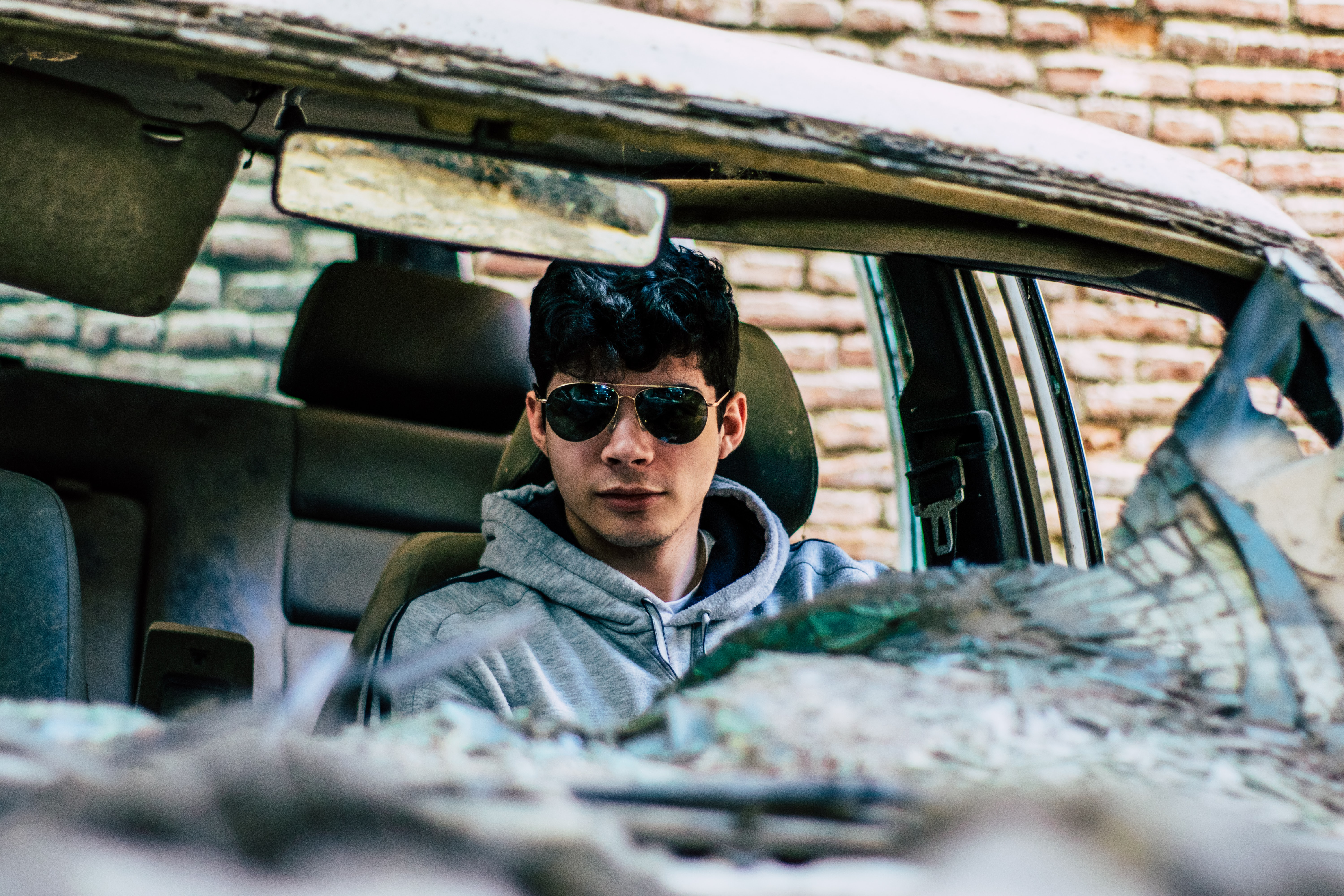 man wearing gray hoodie and sunglasses inside wrecked car
