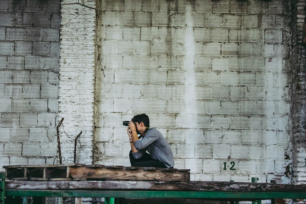 person taking photo near white concrete wall