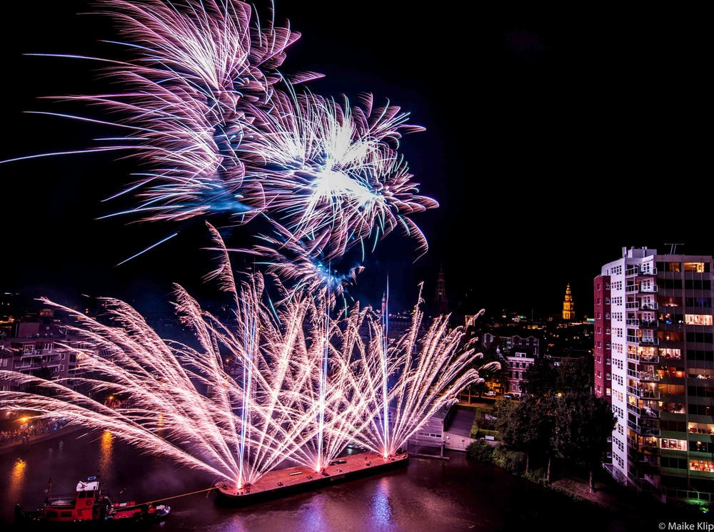 aerial photography of fireworks near buildings at nighttime