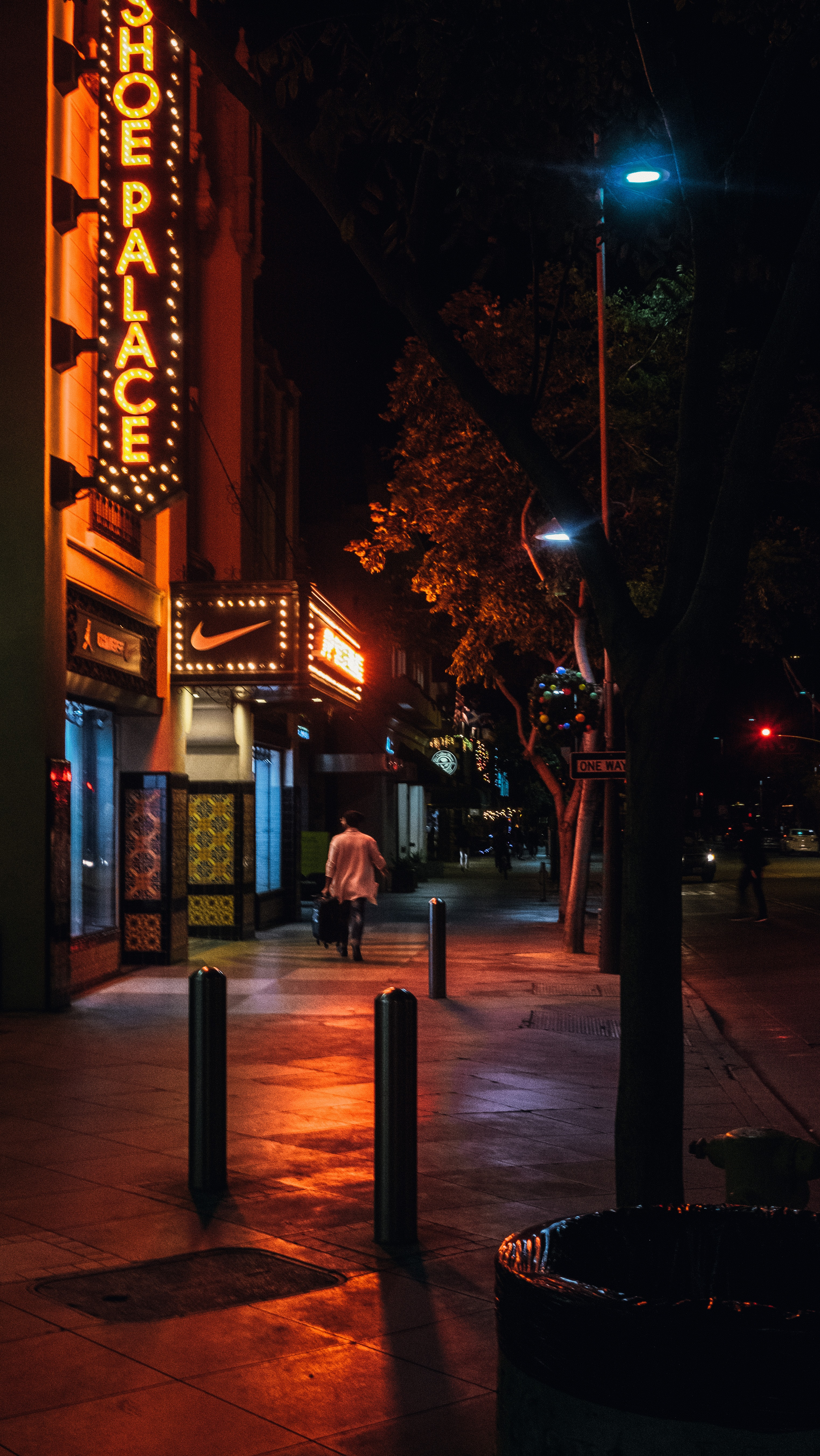 photo of person walking beside a storefront during night time