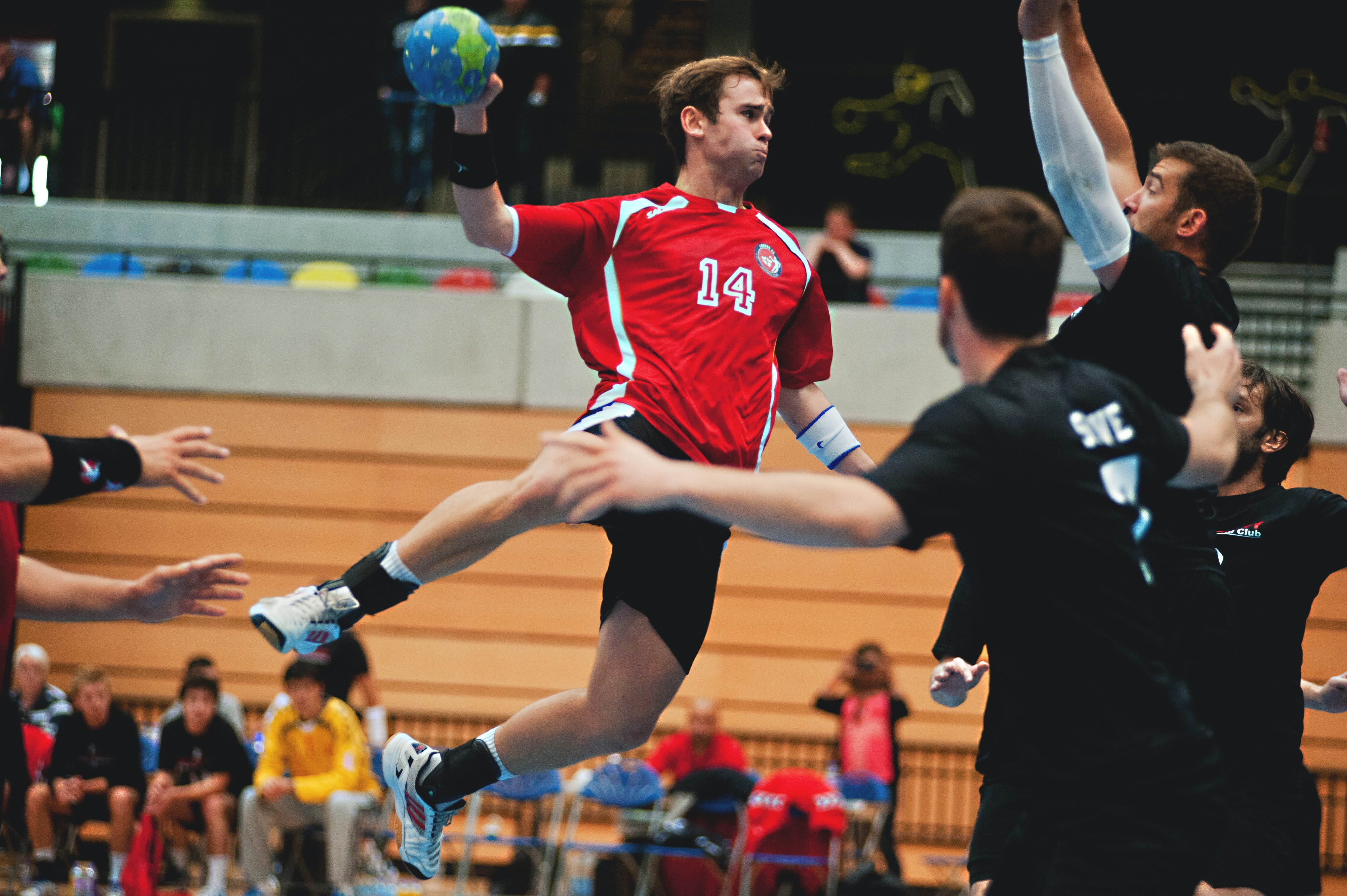 man holding ball while jumping near three mne