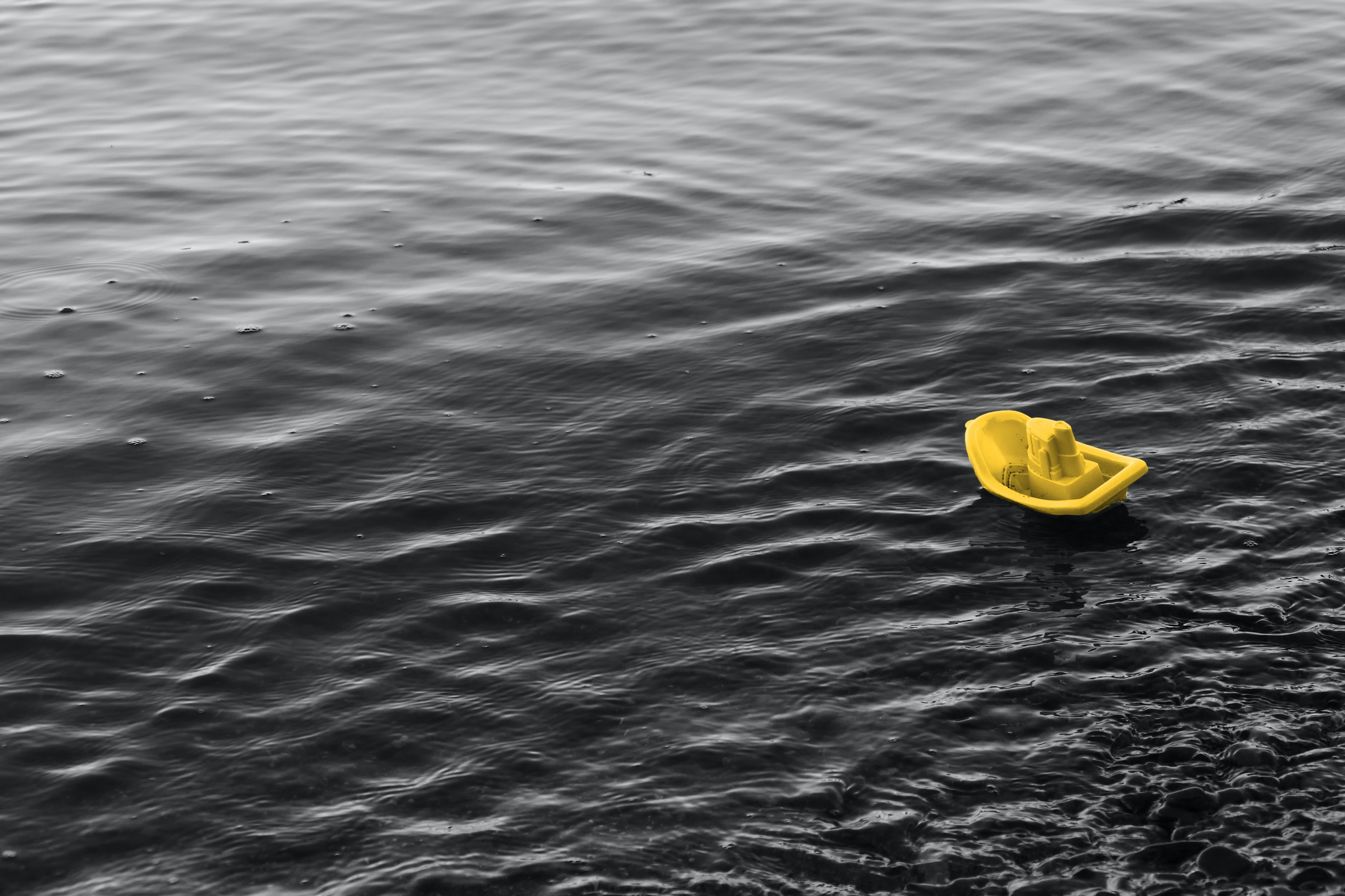yellow plastic ship toy floating on water