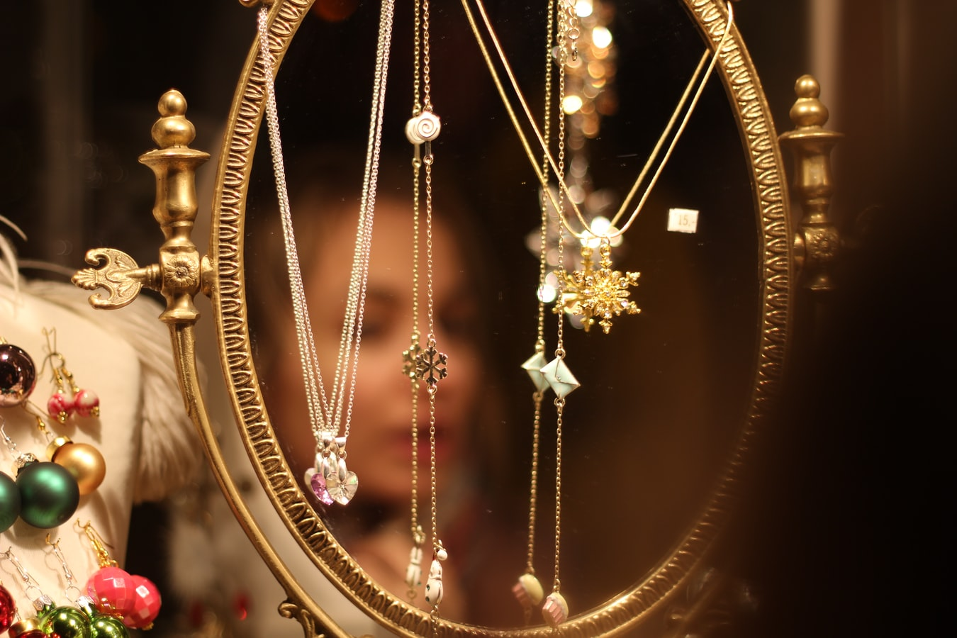 Jewellery. A number of necklaces hanging in front of a mirror. An out of focus womans face can be seen in the reflection.