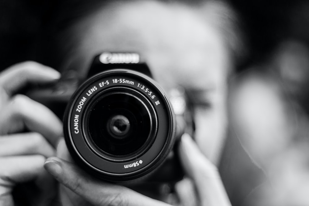 person taking photo using Canon camera in shallow focus lens