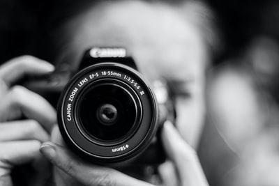 person taking photo using canon camera in shallow focus lens photographer zoom background