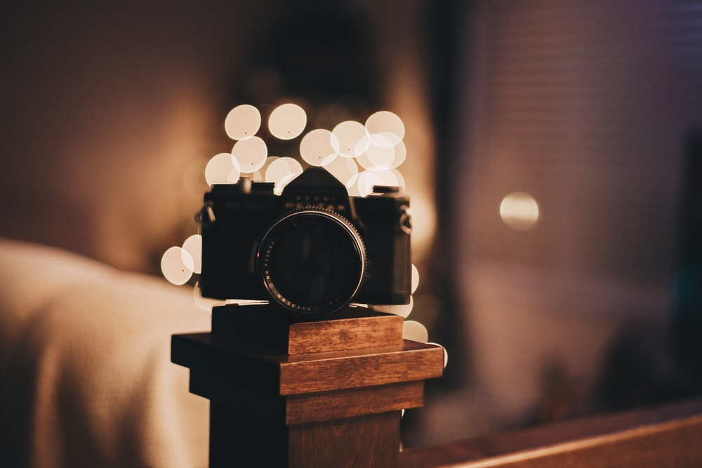bokeh photography of camera on brown wooden baluster