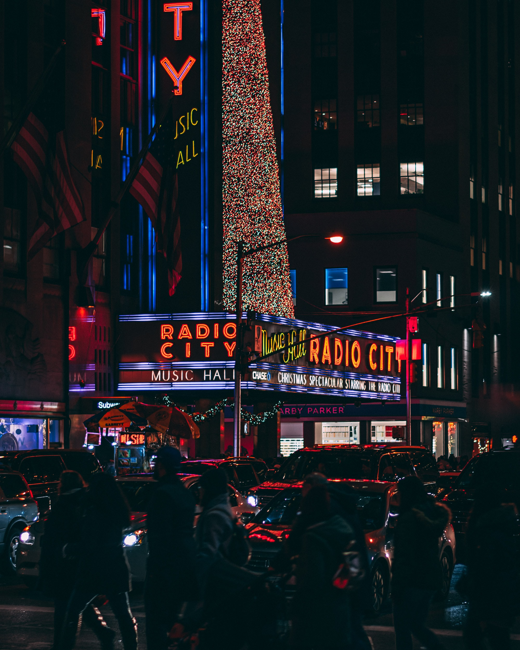 people and vehicles near building with neon lights