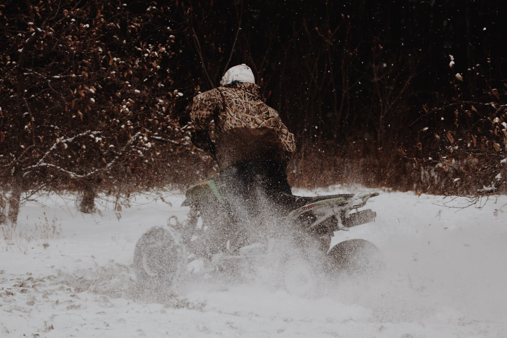 person using ATV on snow ground during daytime