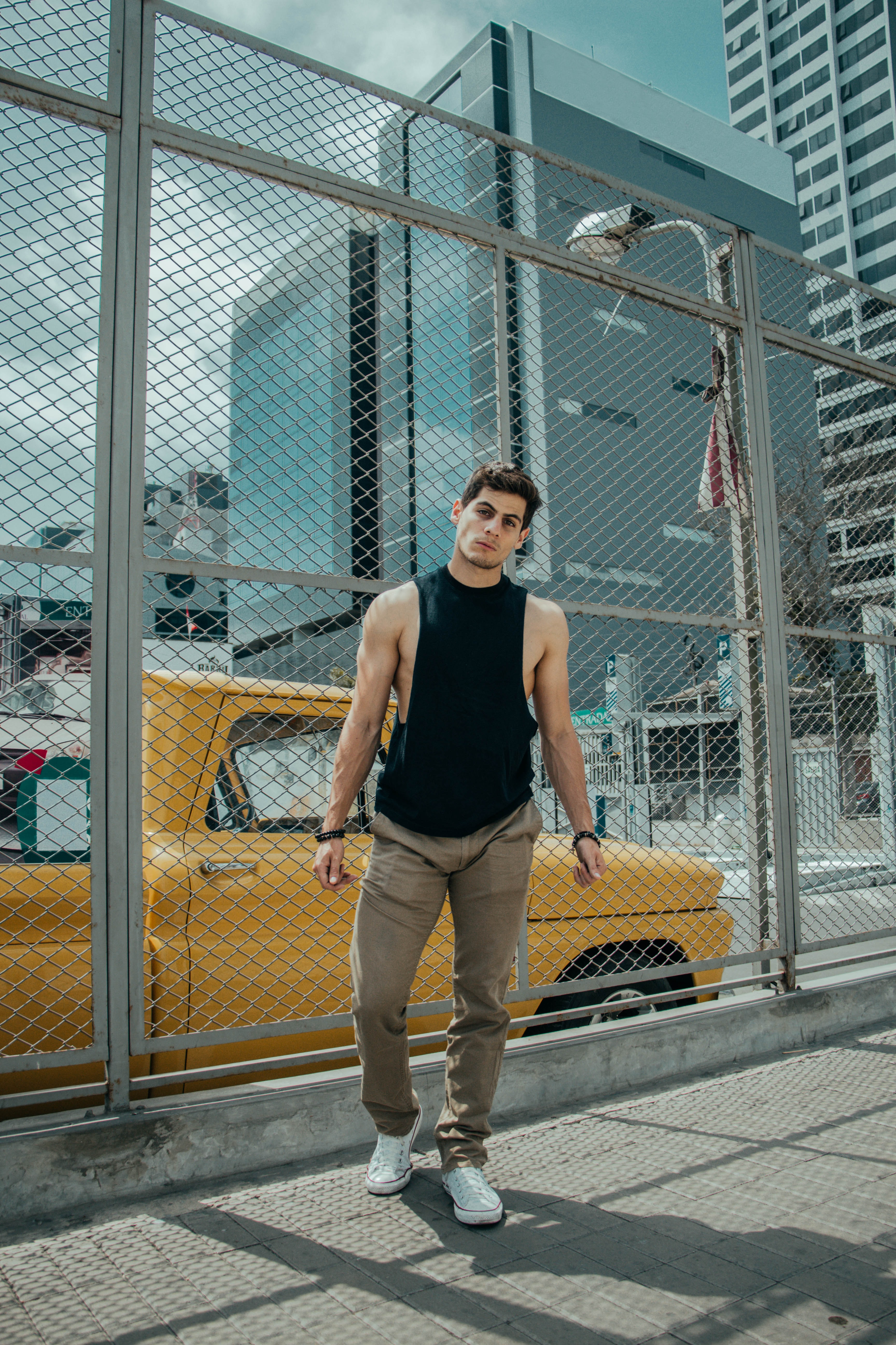 man in black tank top and brown jeans standing beside of wire fence during daytime