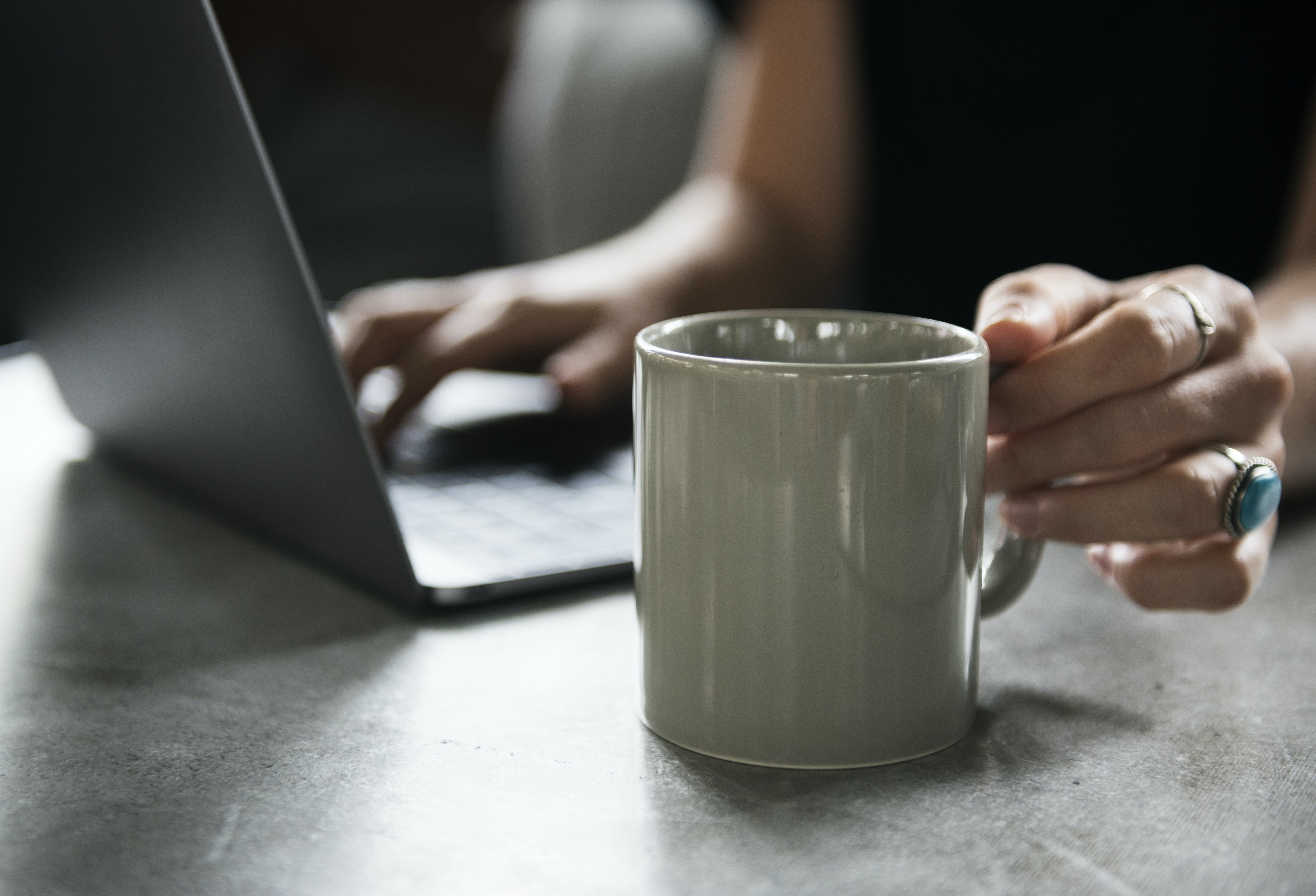person holding gray ceramic mug while using laptop computer