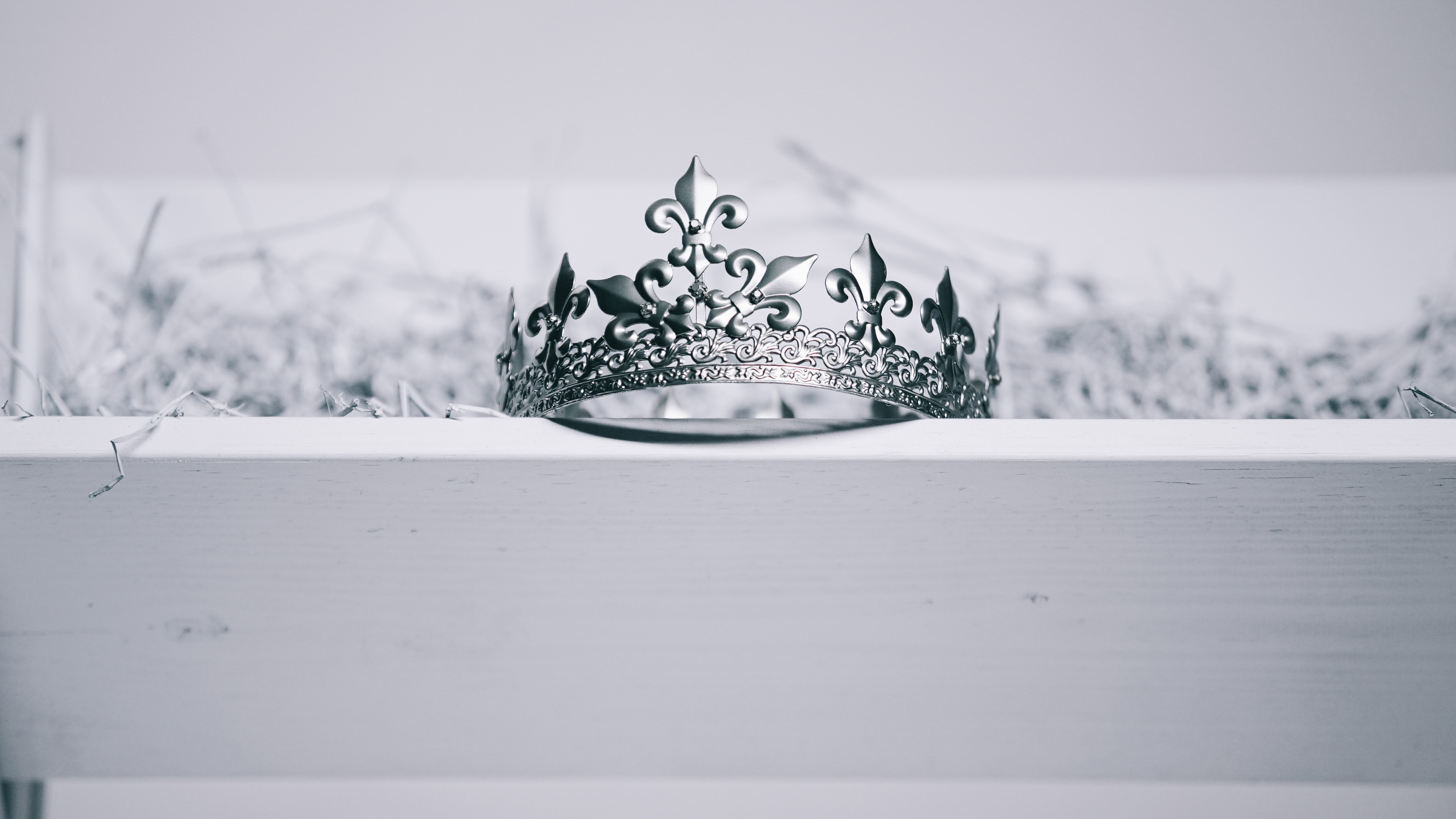 silver-colored crown on top of white wood