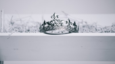 silver-colored crown on top of white wood manger teams background