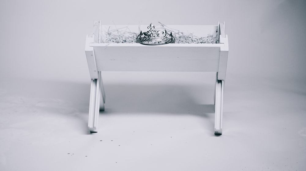 grayscale photography of tiara on table