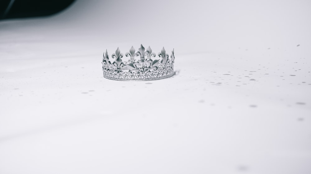 silver-colored crown ring on white surface