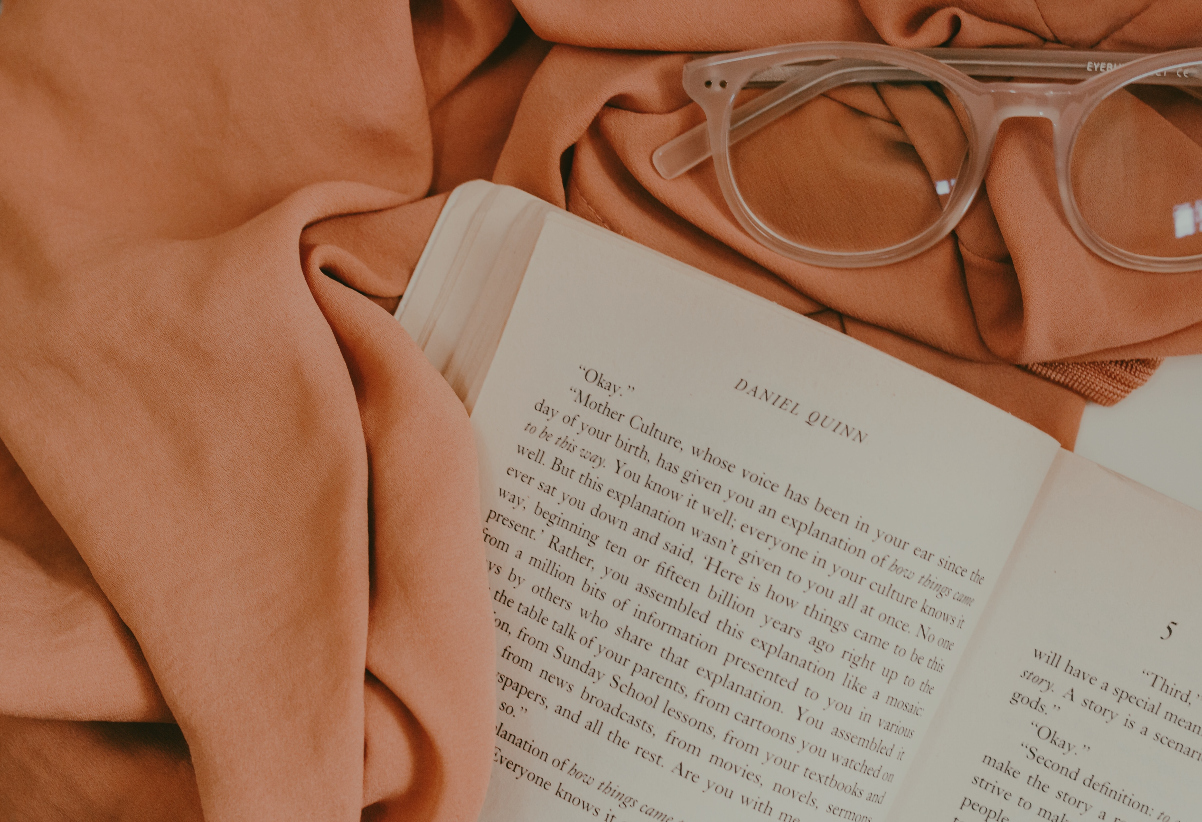 opened book page on top of pink mat near eyeglasses