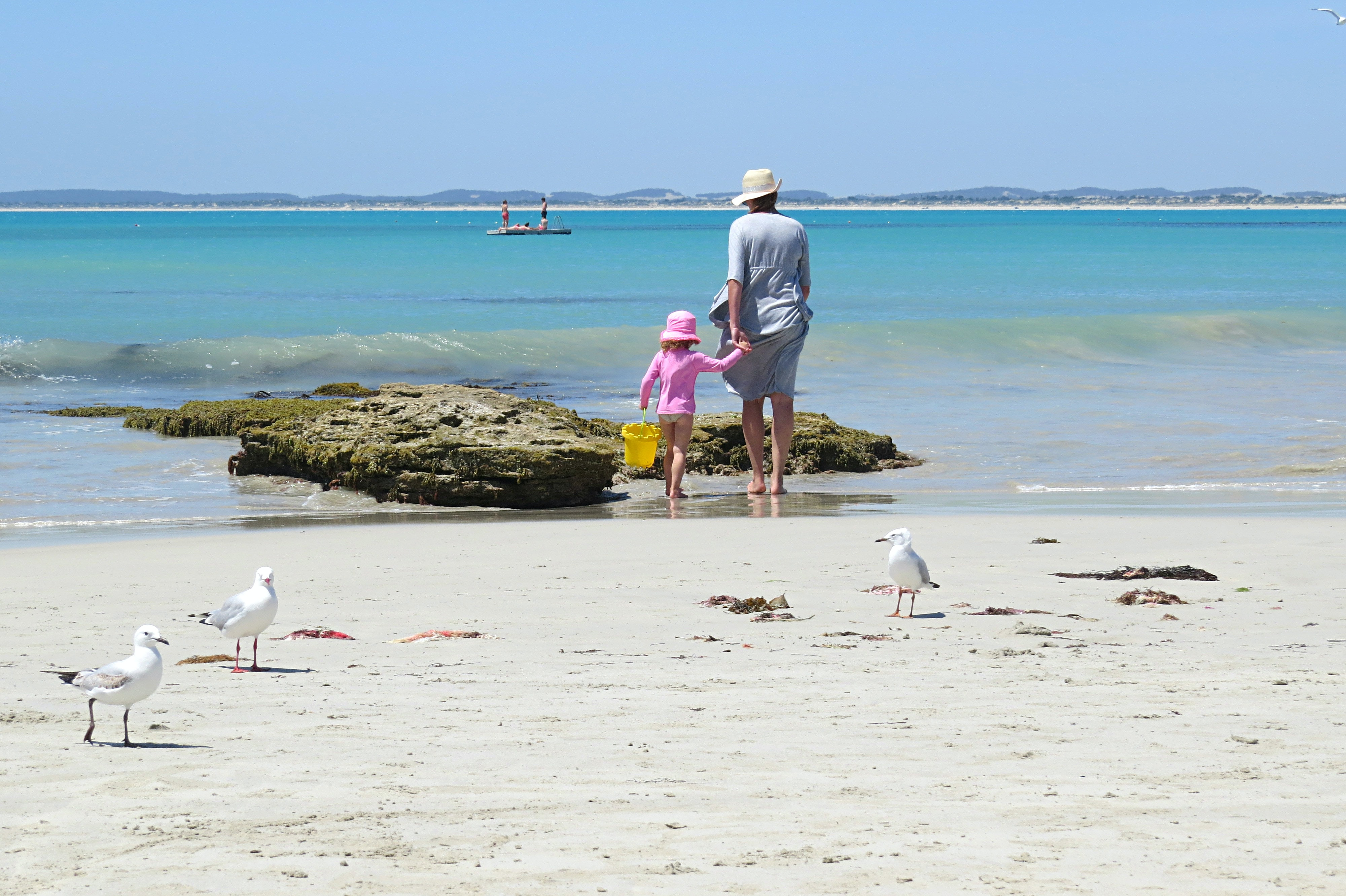 woman holding girl near beach during daytime