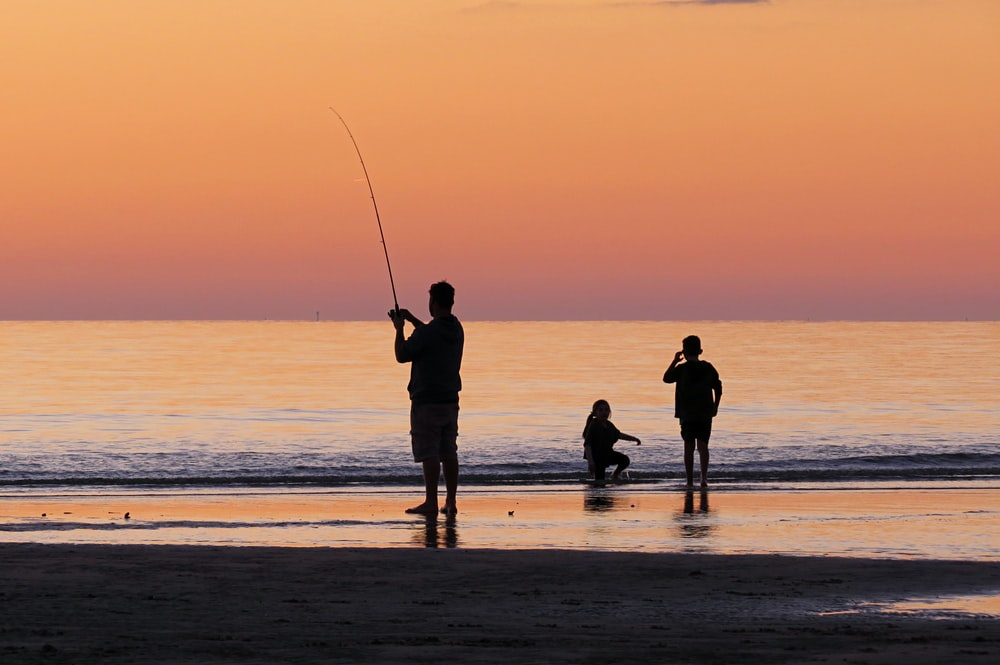 silhouette photo of a man fishing near shore during golden time