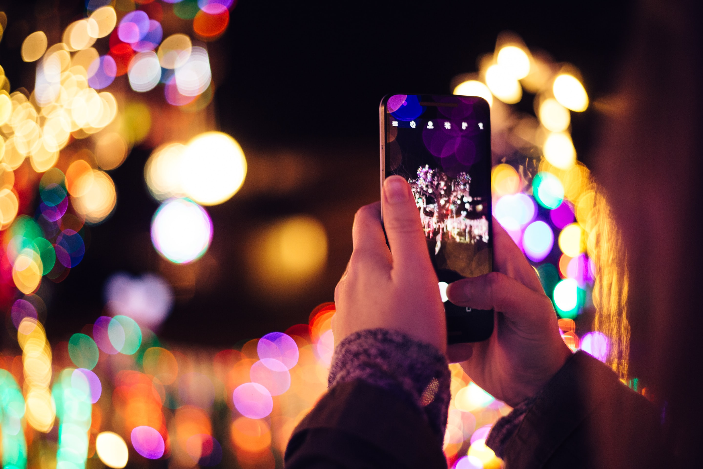 person taking photo of lights during nightime