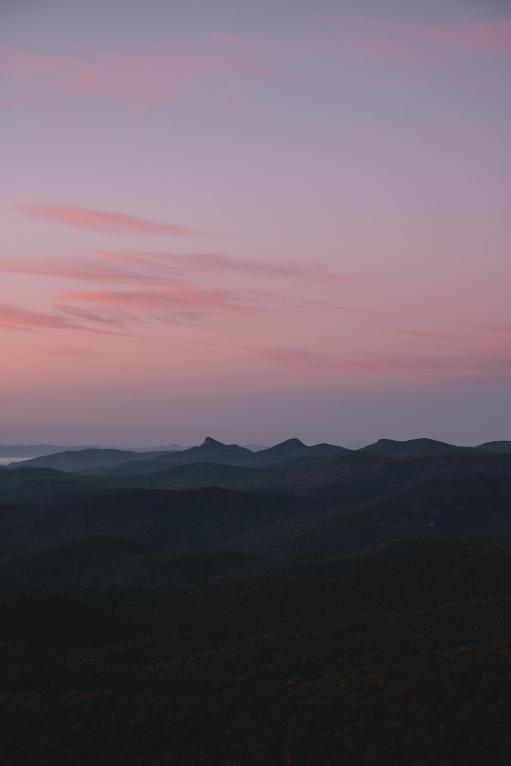 silhouette of mountains under pink sky