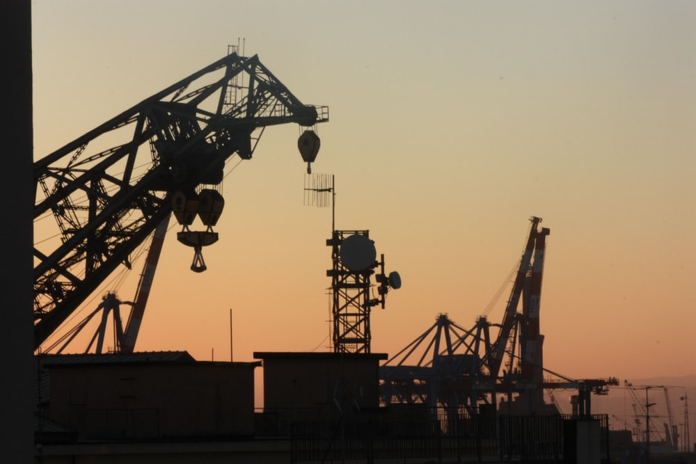 silhouette of metal cranes at worksite during golden hour