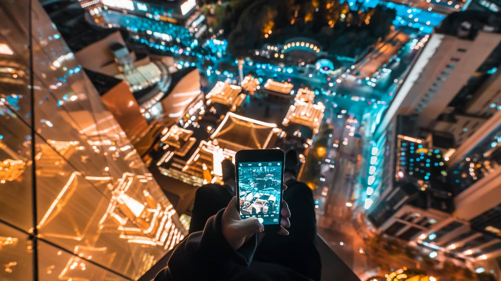 person on skyscraper taking a photo of building below during nighttime