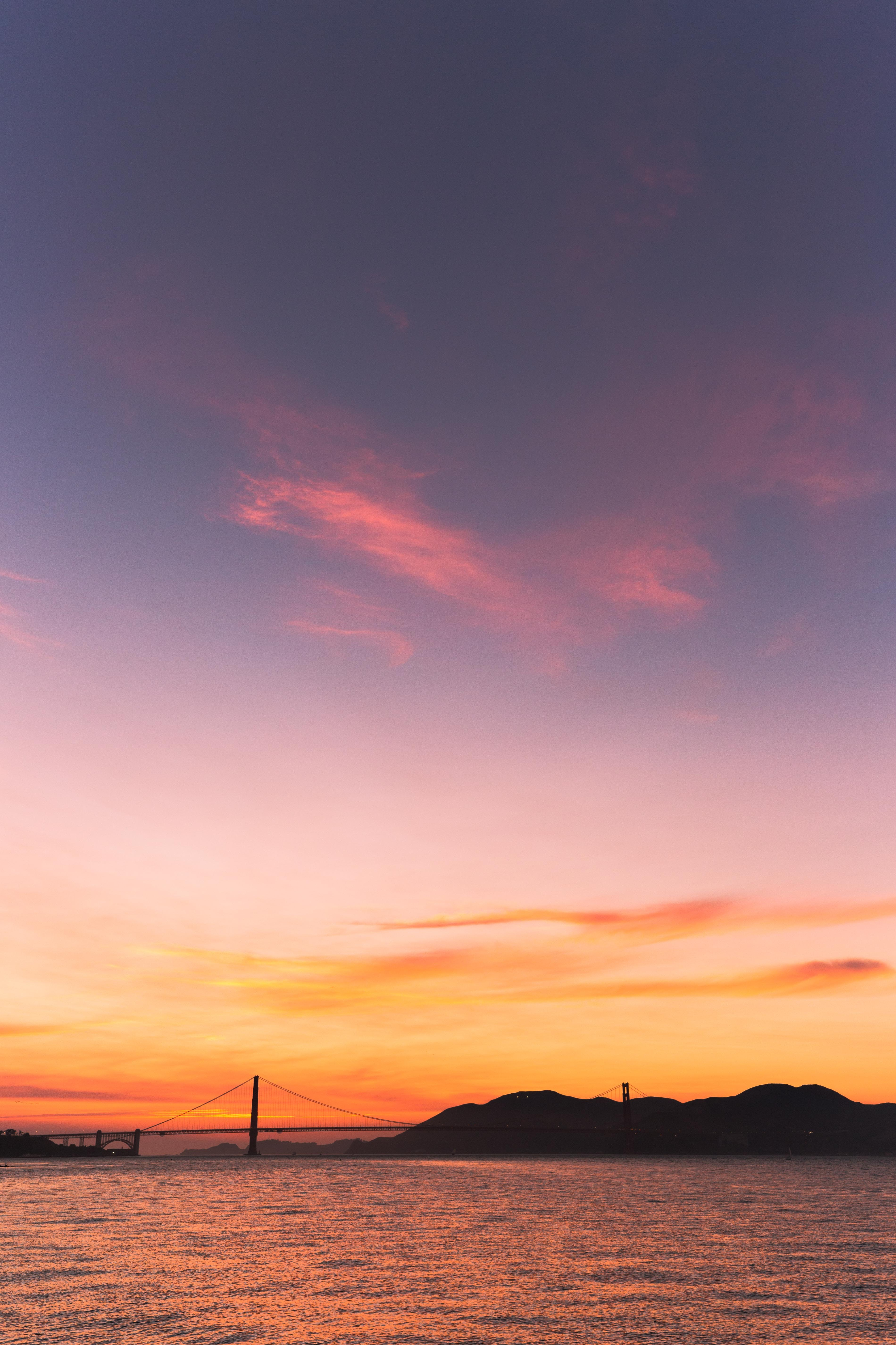 silhouette photography of mountain beside suspension bridge during golden hour