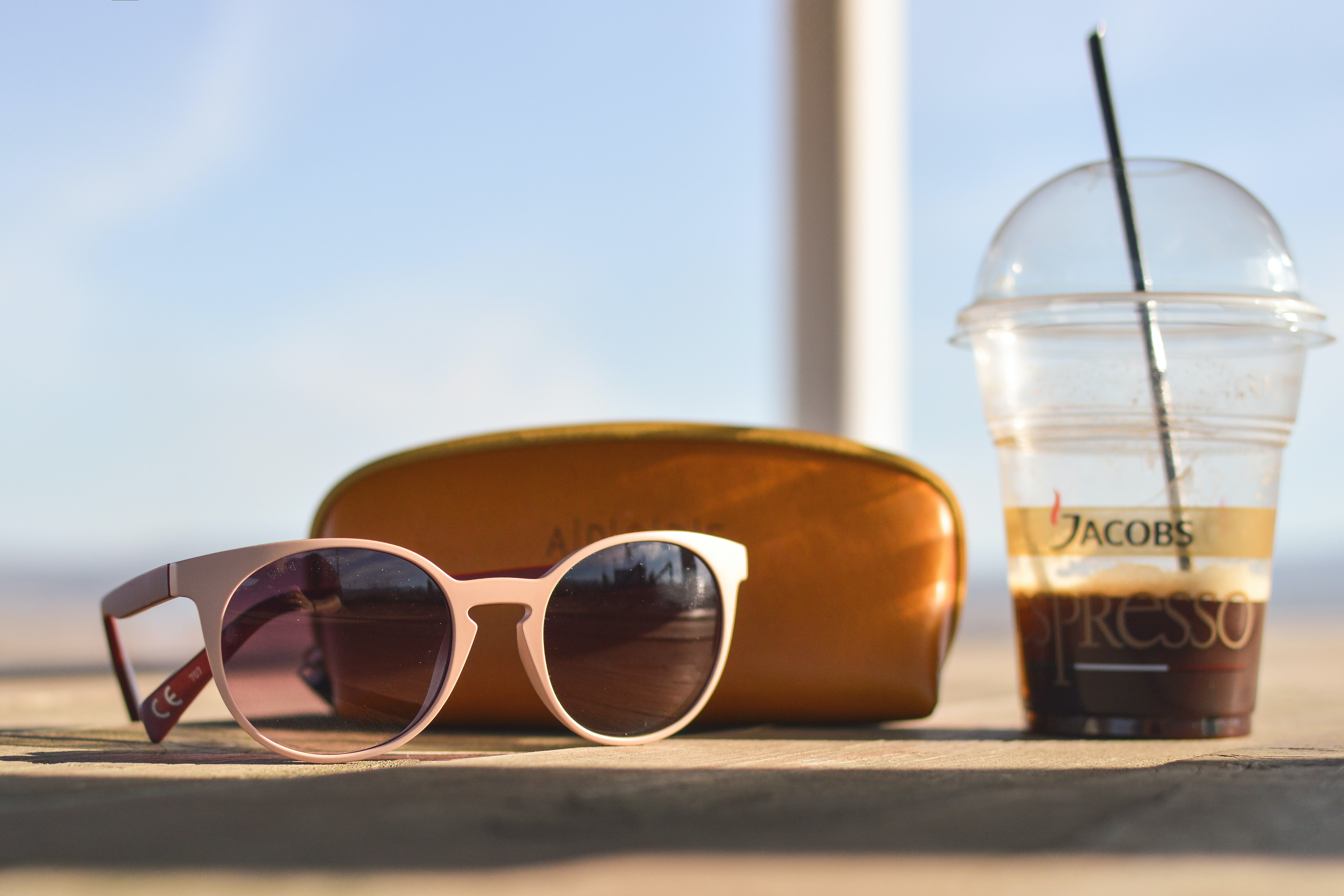 selective focus photography of white sunglasses near brown leather pouch and clear Jacobs Espresso disposable solo cup