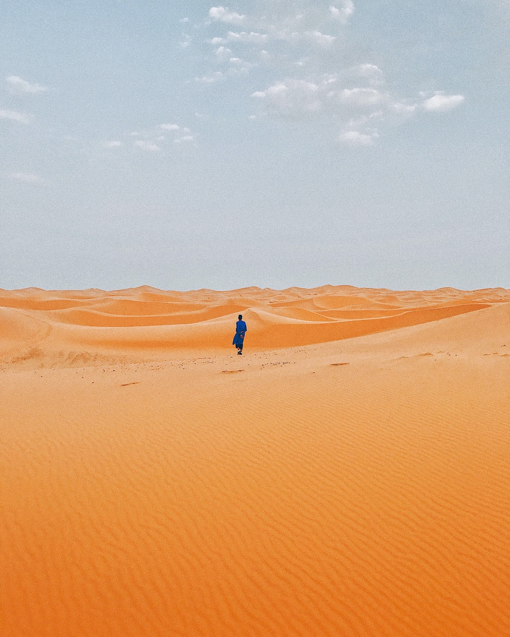 person standing in middle of desert at daytime