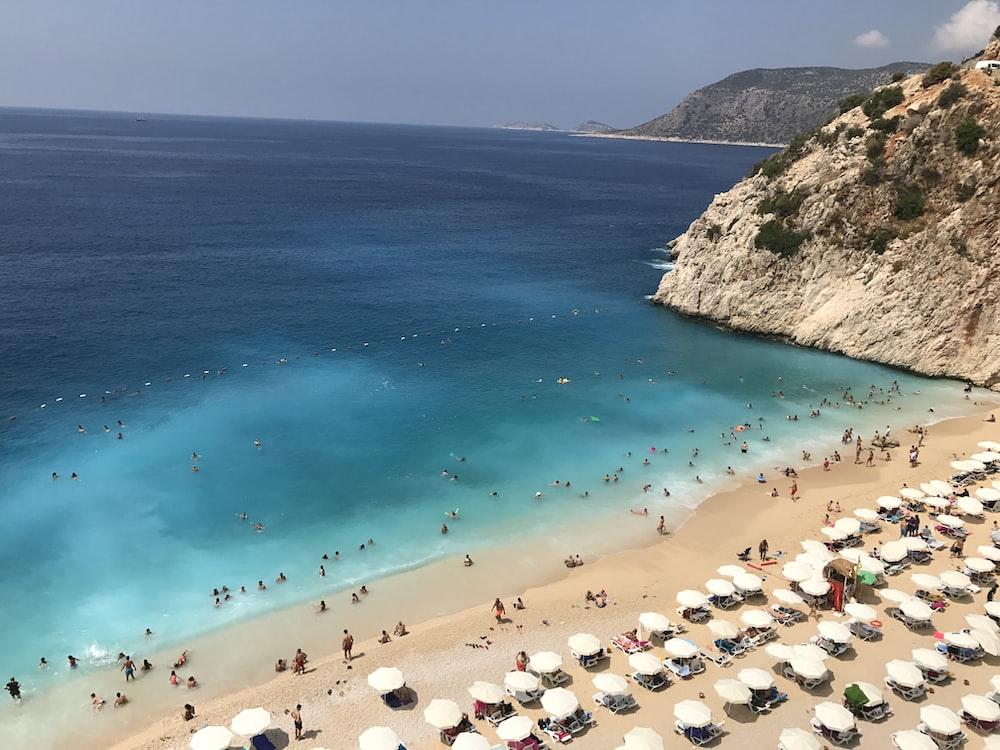 high angle photo of people gathering on seashore near mountain cliff