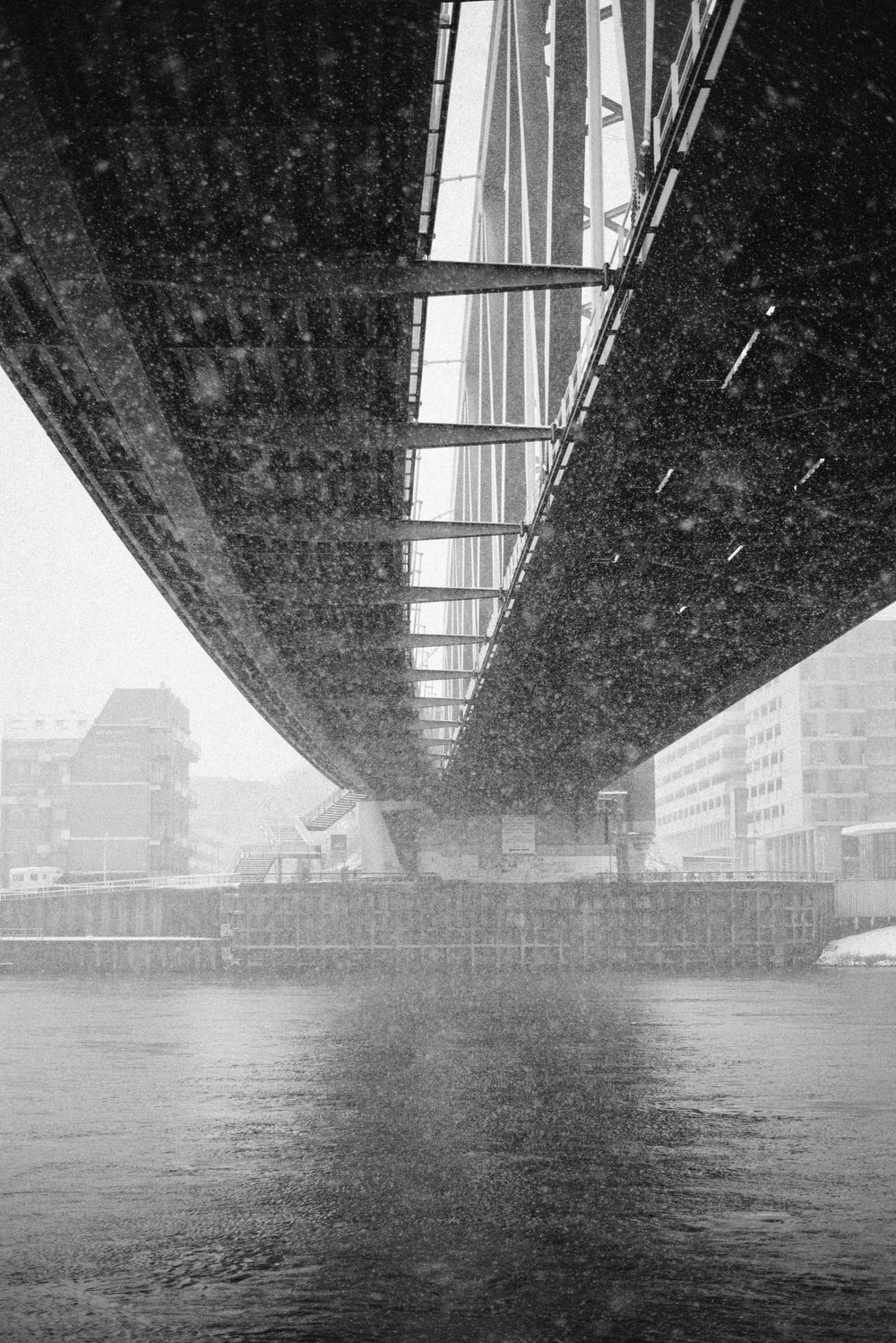 grayscale architectural photography of metal bridge underneath